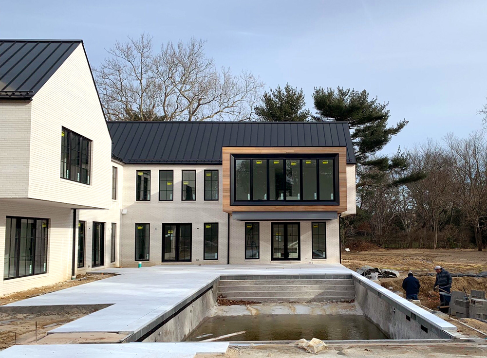 Construction Progress and Home Design for Modern Farmhouse with white brick and black window frames on Long Island, NY